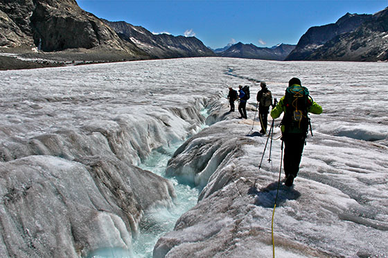 A large stream of water runs down the glacier.