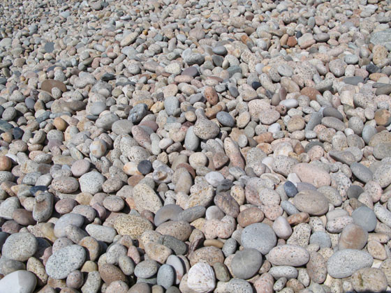 It's actually made of large and perfectly smooth granite pebbles   some as big as a melon   This accumulation of large pebbles gives an idea about what the sheer power of the winter storms must be like